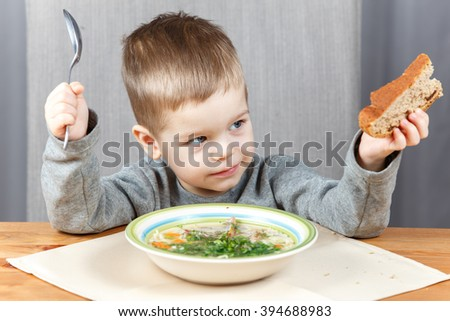 Young boy looking at piece of bread in his hand