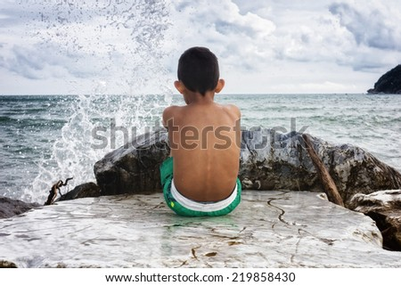 young boy looking at the sea - stock photo