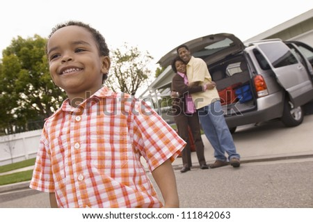 Young boy looking away with parents in background embracing each other