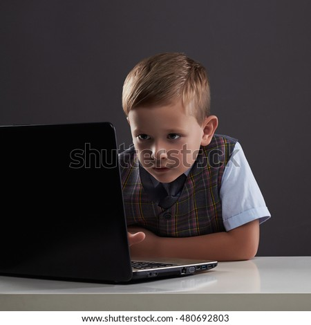 Young boy looking in the notebook screen. funny child with computer. internet technology