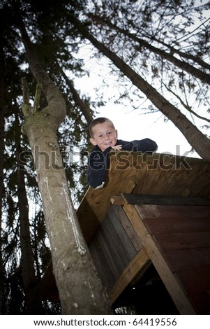 Young Boy looking out from the top of a tree hut - stock photo
