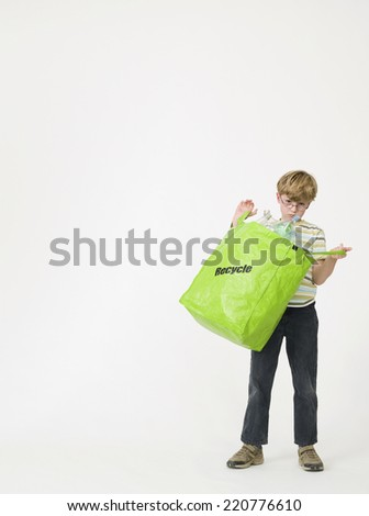 Young boy looking to camera while holding open a green bag with plastic items for recycling shot on a white background - stock photo
