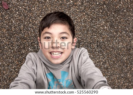 Young boy looking up at the camera from the ground.