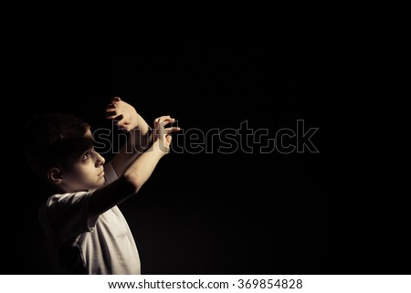 Young Boy Looking Up While Covering Light with his Hands Against Black Background with Copy Space. - stock photo