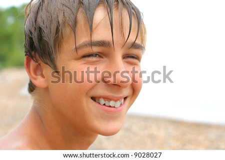 young boy looks aside and smile - stock photo