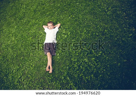 Young boy lying in the grass  - stock photo