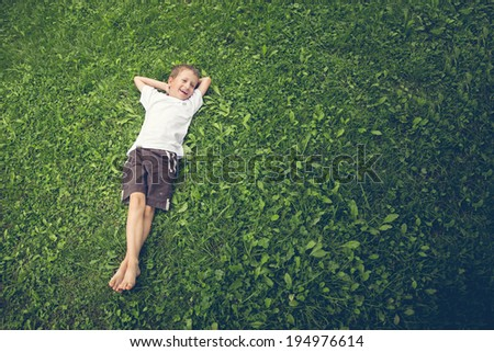 Young boy lying in the grass and laughing - stock photo