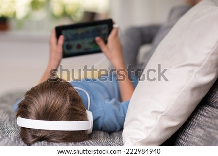 Young boy lying listening to music or an e-learning class on his tablet computer attached to a pair of headphones, view from the top of his head - stock photo