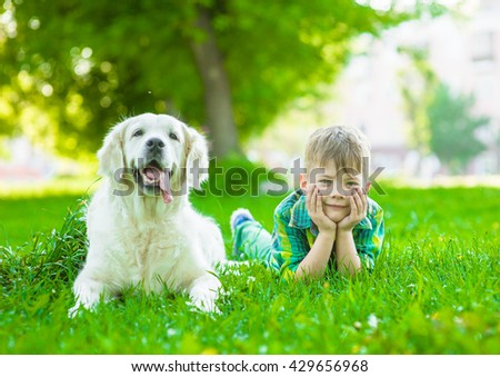 Young boy lying with golden retriever dog on green grass - stock photo