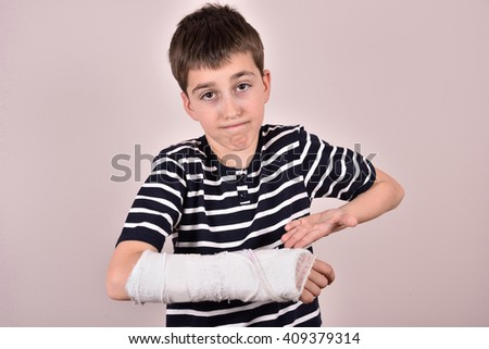 Young boy making a grimace and showing his broken arm with plaster  - stock photo