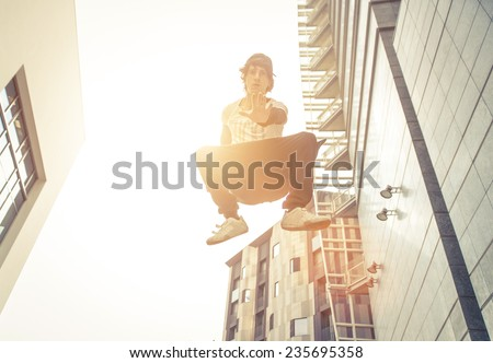 young boy making an high jump while performing parkour - stock photo