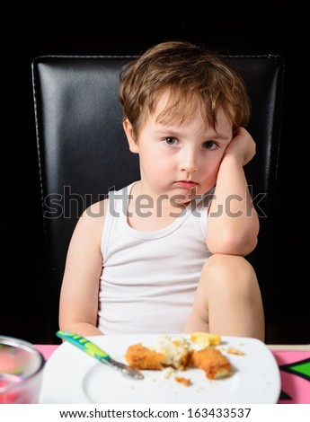 Young boy not happy being told to finish his meal