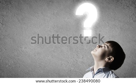 Young boy of school age looking question mark - stock photo