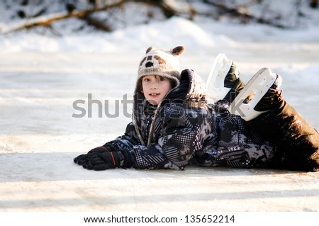 young boy on a frozen pond wearing ice skates - stock photo