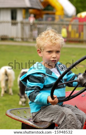 Young boy on a tractor - stock photo