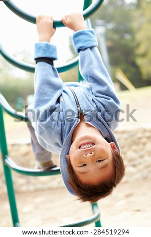 Young Boy On Climbing Frame In Playground - stock photo
