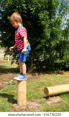 Young boy on obstacle course in playground - stock photo