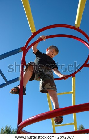 Young boy on playstructure with deep blue sky. - stock photo