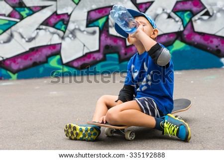Young Boy on Skateboard Taking a Break - Full Length of Boy Sitting on Skateboard and Drinking from Plastic Water Bottle in front of Graffiti Covered Wall in Skate Park - stock photo