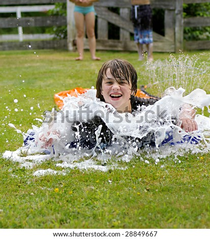 Young boy on slip and slide having fun with over flowing bubbles - stock photo