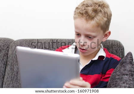 Young boy on tablet pc - stock photo