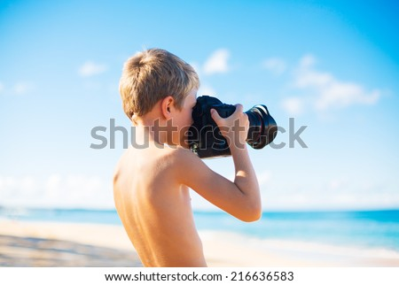 Young Boy on the Beach Taking Photograph with Professional Camera