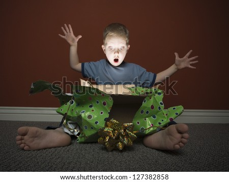 Young boy opening present sitting on the floor - stock photo