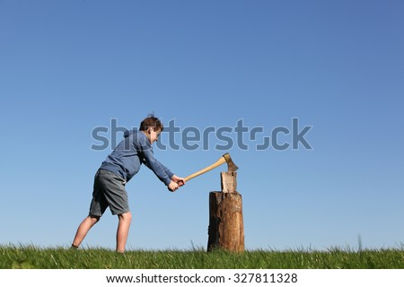 Young boy outdoors chopping wood with blue sky