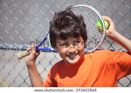 Young boy outside in sun with tennis racquet and ball - landscape format with copy space above - stock photo