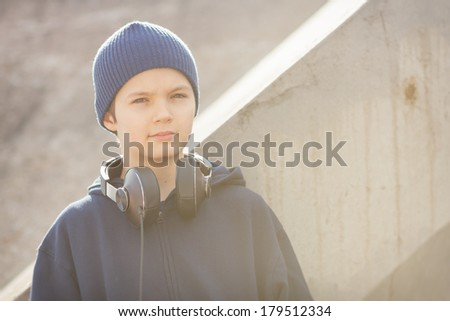 Young boy outside in urban environment with headphones in vintage look