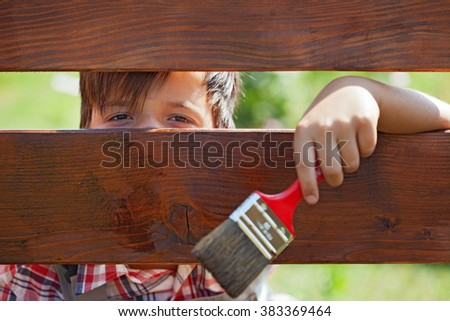 Young boy painting the wooden fence - peeking through the planks - stock photo