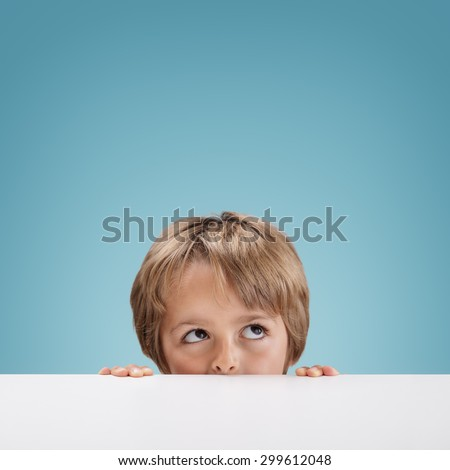 Young boy peeking over a white board looking up at copy space for a message - stock photo