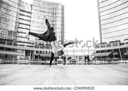 young boy performing parkour move in the center of Milan. concept about recreation and leisure - stock photo