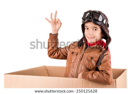 Young boy pilot flying a cardboard box isolated in white - stock photo