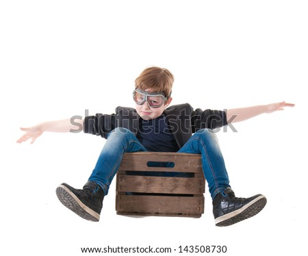 Young boy pilot flying a wood box isolated in white