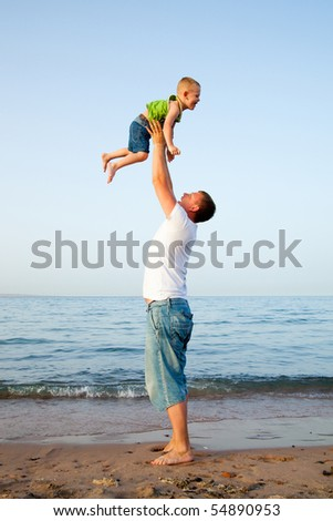 Young boy play with father. Father throwing his son into the air. On a beach.