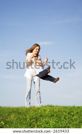 Young boy play with mother. Blue sky. Green grass. 5 - stock photo