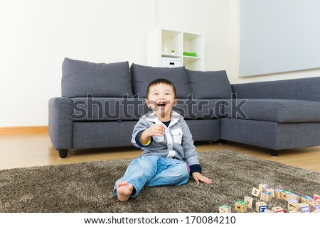 Young boy play with wooden toy block - stock photo
