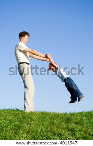 Young boy played with father. Green grass. Blue sky. 11 - stock photo
