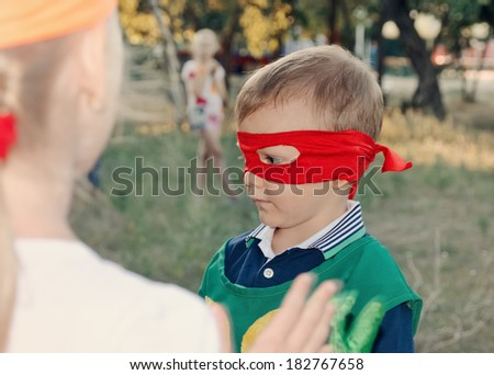 Young boy playing at a kids birthday party wearing a super hero mask as he chats to his young friends - stock photo