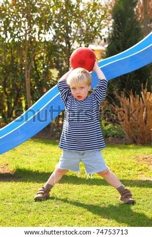 Young boy playing ball in the garden - stock photo