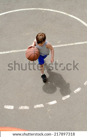 Young boy playing basketball in an outdoor court top view - stock photo