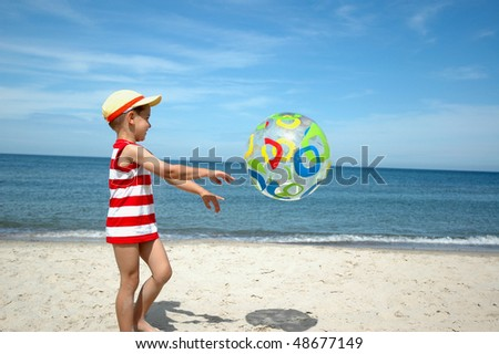 Young boy playing beach ball by the sea