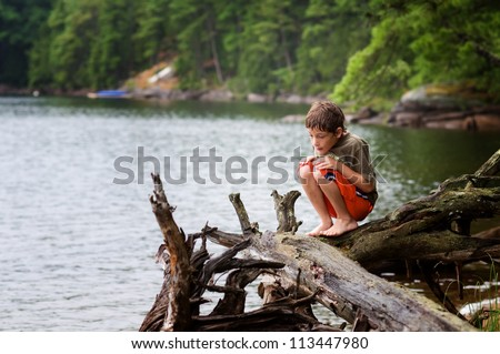 young boy playing by a lake - stock photo