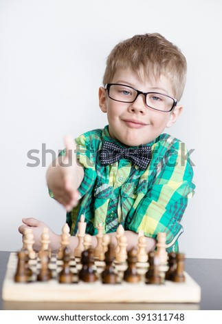 Young boy playing chess, offering hand - stock photo