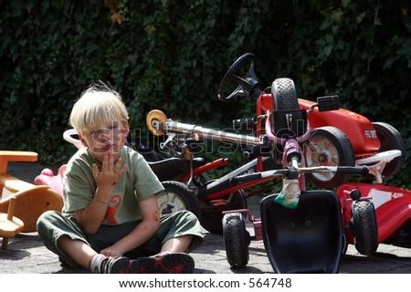 Young boy playing crash victim - stock photo