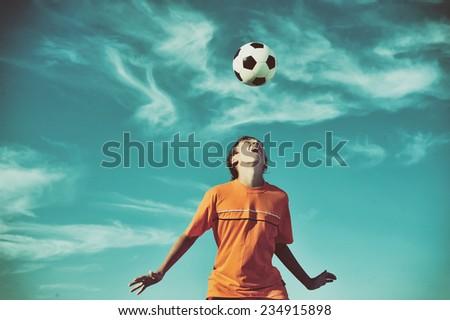 Young boy playing football - low angle virw - stock photo