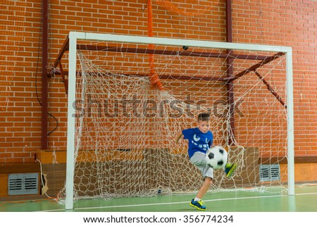 Young boy playing goalkeeper in an indoor sports facility kicking the soccer ball clear of the goalposts as he practices for a game - stock photo