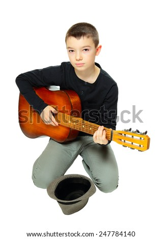 Young boy playing guitar with hat for money on white background  - stock photo