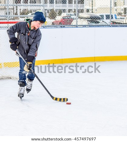 Young boy playing hockey on ice